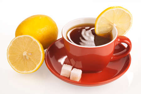 Cup of tea with lemon and sugar cubes on white  photo