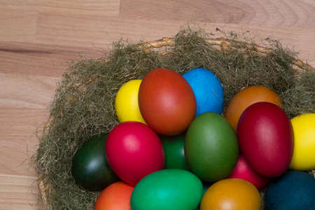 yeloow: Colorful eggs in the nest, on wooden surface