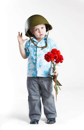 Boy with army helmet and carnations, isolated on white photo