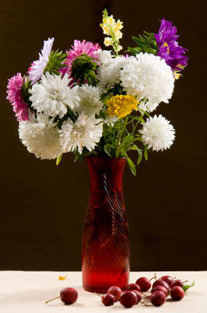 red vase with a bouquet of multicolored aster and apples photo