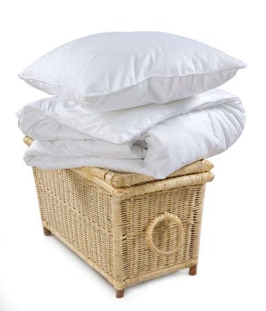 kussen en deken op rieten mand geïsoleerd op een witte achtergrond Stockfoto