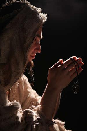 praying man in monks clothing Stock Photo