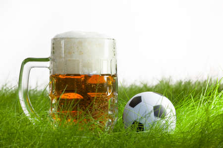 mug of beer and soccer ball on grass in white  Stok Fotoğraf
