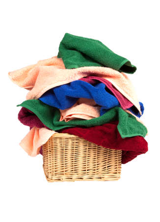 pile of towels in a basket isolated on white background photo