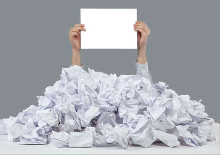 chafe: Hands with empty paper reaches out from big heap of crumpled papers