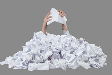 chafe: Hands with empty crushed paper reaches out from big heap of crumpled papers Stock Photo