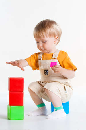 boy is sitting on his haunches and playing cubes, isolated on white background photo