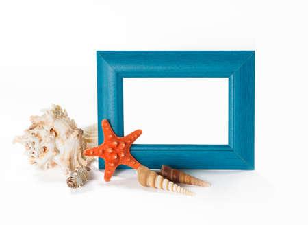 Blue photoframe with seashells near it, isolated on white background photo