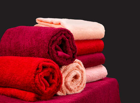 stack of colorful terry towels on a table isolated on dark background