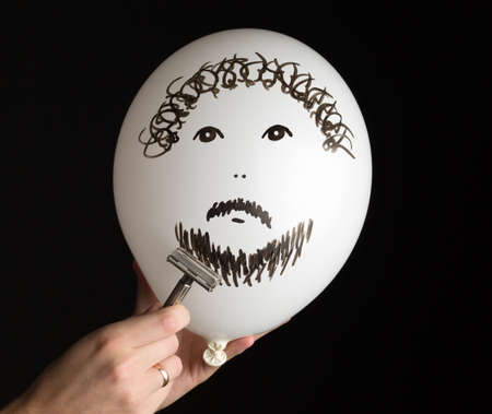 firmness: hand shaves a white ballon on a black background