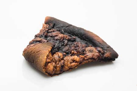 unskilled: burnt slice of pizza on white background