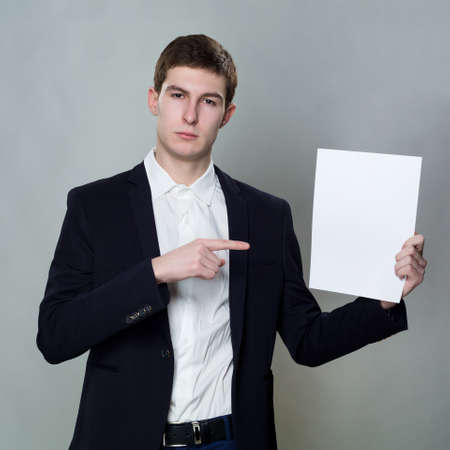 specifies: young business man with empty white paper on gray background