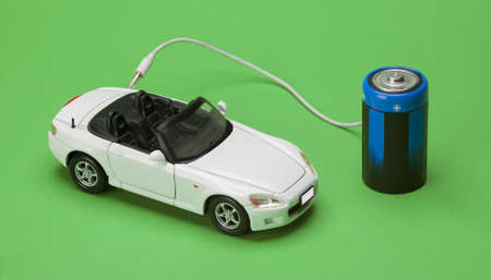 the eco car powered by batteries on green background