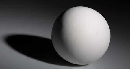 white ball with shadow on gray background
