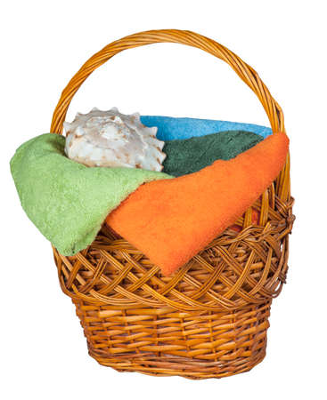 wooden basket with towels and shell isolated on white background