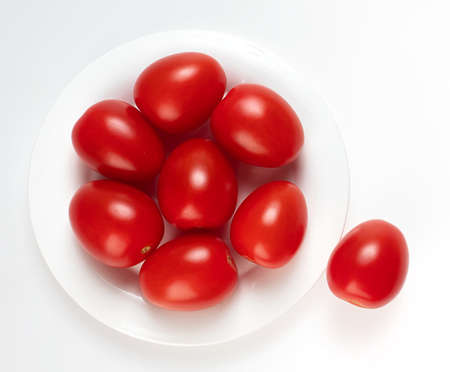 fresh red tomatoes on a round plate on a white background