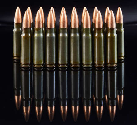 metal cartridges for hunting automatic weapons on a black background with a reflection Foto de archivo