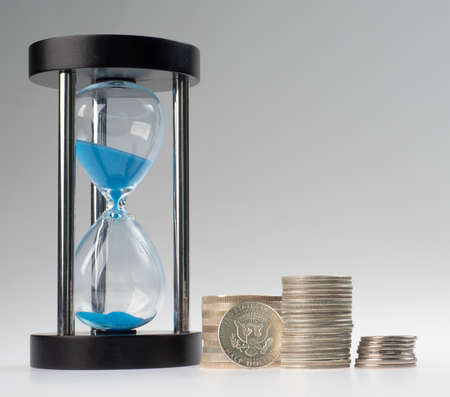 time and money. stacks of coins and an hourglass on a gray background