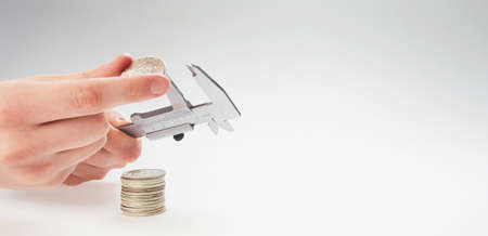 finance. hands holding calipers and silver coins on a light background
