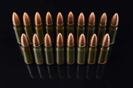 metal cartridges for hunting automatic weapons on a black background with a reflection