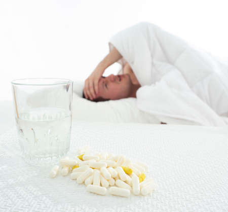 Tired sick  man on couch under blanket with tablets and thermometer on white background