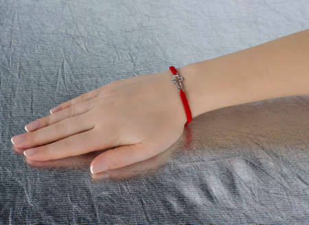 red thread with a cross on the hand of a girl. close-up