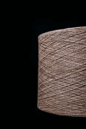 a skein of thick thread on a dark background. Vertical photography Фото со стока