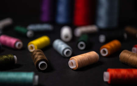 Multi-colored threads are scattered on a dark background.