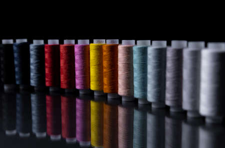 needlework, craft, sewing and sewing concepts - row of colorful thread spools on table with reflection.