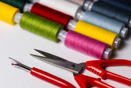 Spools with multi-colored threads and scissors on a light background. Sewing and handicraft accessories.