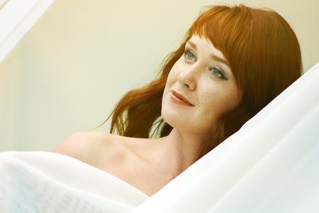 Portrait of a beautiful redheaded woman looking flirtatious.