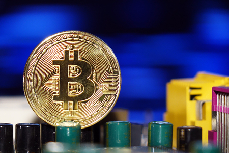 Cryptocurrency bitcoin gold. Bitcoins on the motherboard.