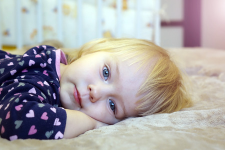 Beautiful child lying on the bed.