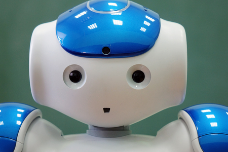 A small robot with a human face and a humanoid body. Artificial intelligence - AI. Blue-and-white robot. Stock Photo