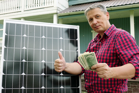 Solar panel. Money in the hands of men . Energy production technologies. Wooden house background. Saving. Banque d'images - 104278891