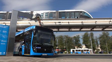 Moscú, Rusia-septiembre de 2017: El concepto de transporte urbano. Autobús eléctrico azul en la estación de carga. Tren moderno que pasa en el monorraíl. El concepto de futuro ecológico.