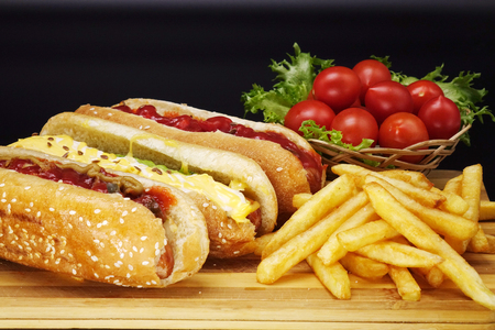 Hot dogs and French fries on black background. Sausages with tomato sauce and cherry tomatoes on a wooden Board.