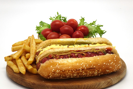 Hot dogs and French fries on white background. Sausages with tomato sauce and cherry tomatoes on a wooden Board.