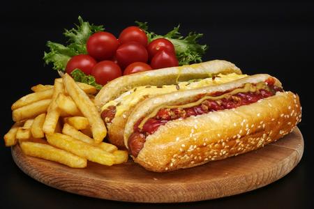 Hot Dogs und Pommes Frites auf schwarzem Hintergrund. Würstchen mit Tomatensauce und Kirschtomaten auf einem Holzbrett.