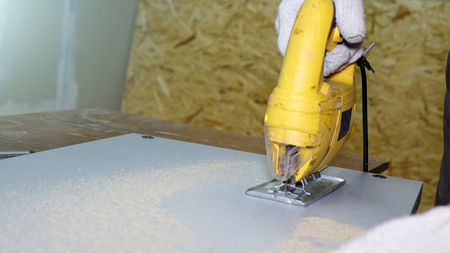Working with an automatic electric saw works in a carpentry workshop. The concept of handmade.