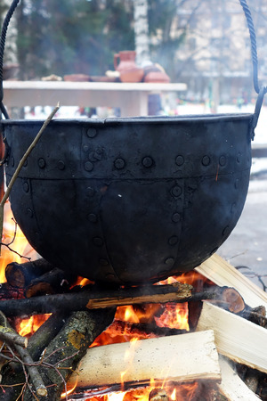 Pot over a fire.Cooking over fire in the woods in winter.