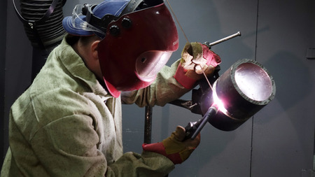 Welder in the mask. The metal product is welded by welding machine