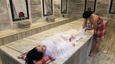 Jeune femme en bikini se détendre dans un hammam. Asiatique est titulaire d'un bain traditionnel dans un bain turc.