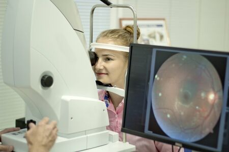 A young woman undergoes an ophthalmological examination, checking the health of the eyes and visual acuity.