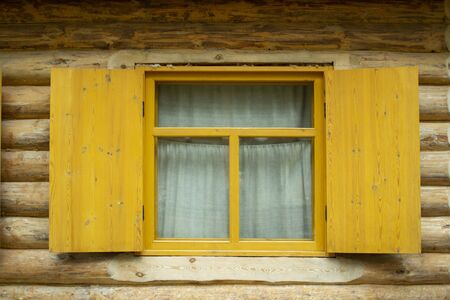 Wooden log house. Window with shutters of a wooden house