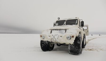 All-terrain vehicle for movement in hard-to-reach places. Car on the snow crust of the lake.