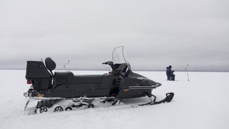 The snowmobile is intended for movement in hard-to-reach places on a snow crust of the lake. Standard-Bild