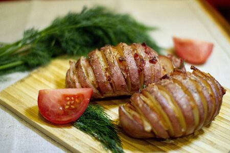 Potato accordion. Garnish potatoes stuffed with bacon and herbs on a wooden stand Stockfoto