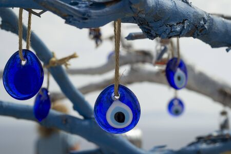 Stone in the form of a blue eye on the tree.Close-up on a tree on chains hang national signs of Turkey-Turkish eyes.