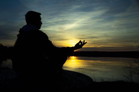 Silhouette eines meditierenden Mannes. Der Typ sitzt im Lotussitz auf einem Stein und schaut in die untergehende Sonne